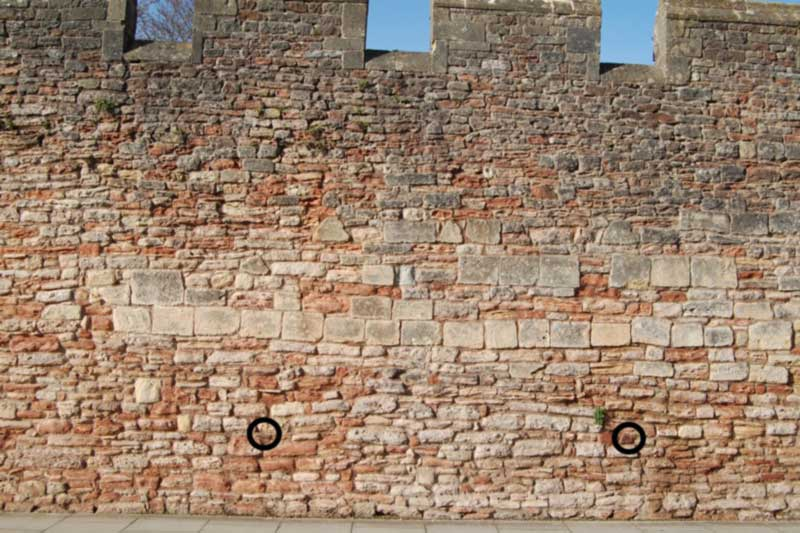 Stone wall between the Old Deanery entrance and the Wells and Mendip Museum on Cathedral Close, opposite the cathedral in Wells.